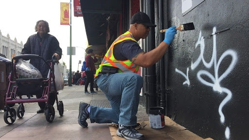 Community ambassador Sakhone Lasaphangthong helps paint a storefront in Oakland's Chinatown.