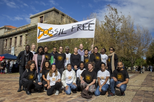 """A group of people pose under a banner that reads """"Fossil Free"""""""