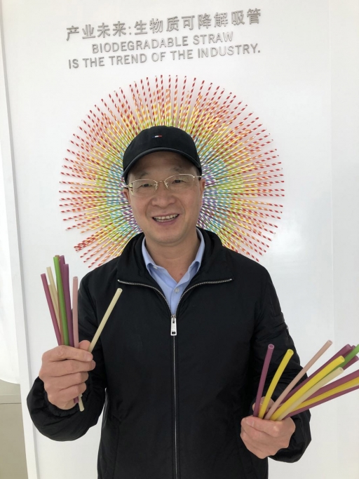 A Chinese man holds straws in both of his hands and smiles