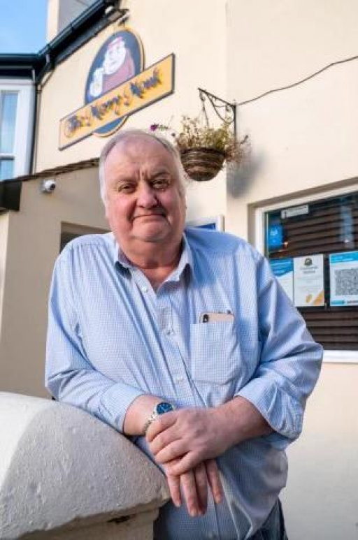 A rotund white man with gray hair smiles and poses for a photo wearing a blue shirt outside one of his pubs, The Merry Monk.