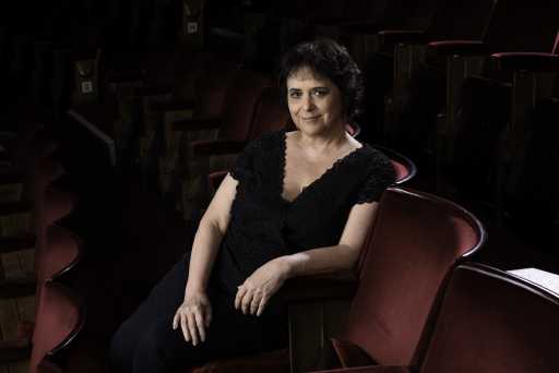 A white woman with dark black hair wearing all black clothing poses seated in a chair at a theater, smiling to the camera with her arms on her lap.