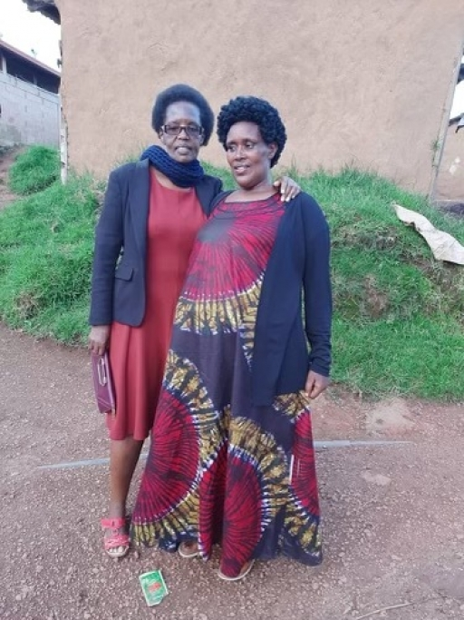 Two women pose together in Rwanda for a photo wearing reddish traditional clothing.