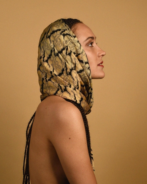 Justine Mauvin, also known as Sibu ManaÏ, featured in a profile pose wearing a gold and black headscarf with light-skinned shoulders showing from the side.