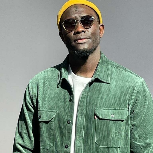 Senegalese artist Lass, a Black man wearing a green jacket, white shirt underneath, with a yellow hat and sunglasses, poses for a photo.