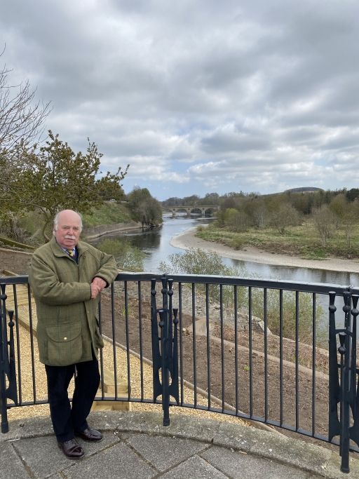 John Greenwell wears a green jacket, black pants and stands near a black fence overlooking a winding river.