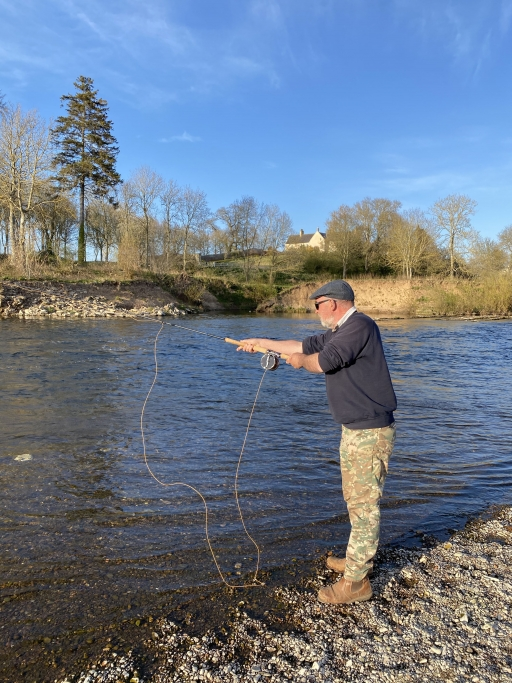 Malcom Campbell leans over the river with a fishing line on a sunny day.