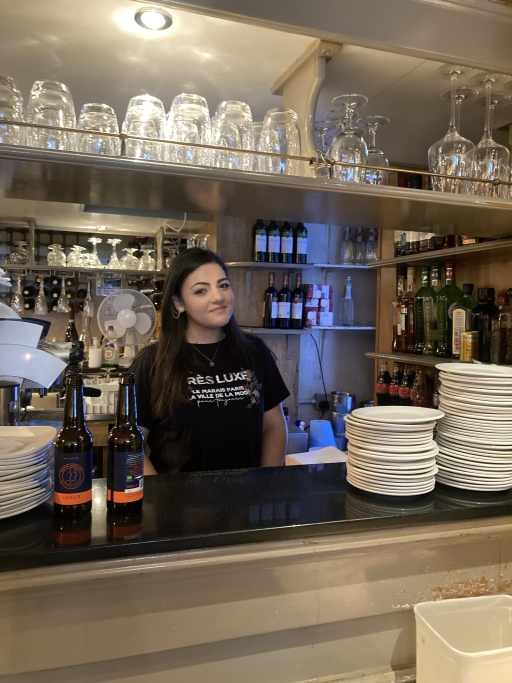 Giada Calabrese, from southern Italy, works behind the bar in a black shirt surrounded by cups and plates.
