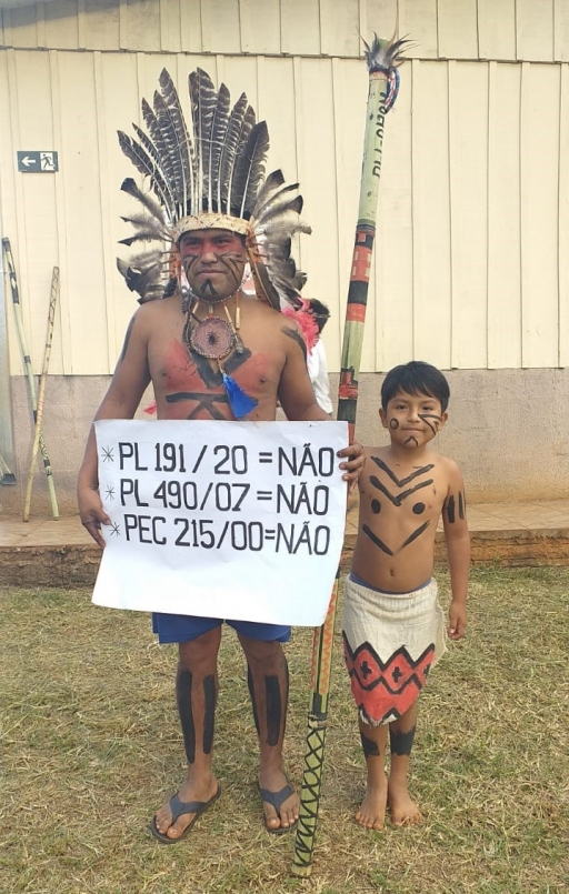 An Indigenous man wearing a feathered crown stands near a small boy and holds a sign.