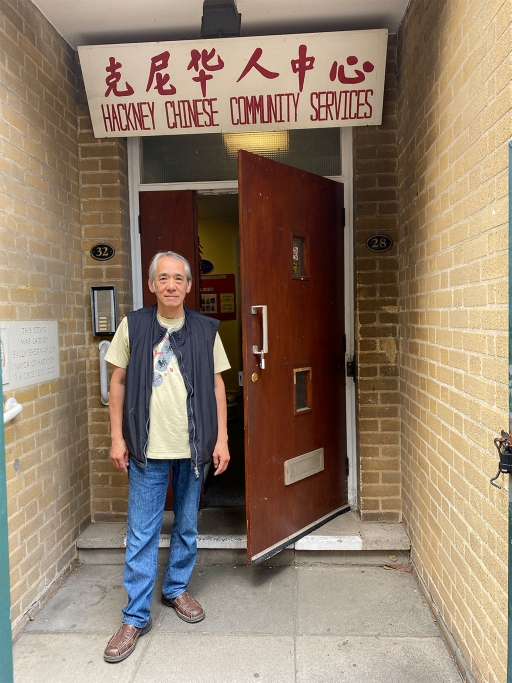A man stands in front of a door with the words 'Hackney Chinese Community Services' written above in Chinese and English.