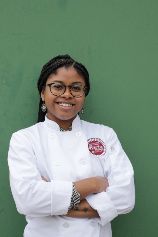 Woman against green backdrop standing and smiling, arms folded, wearing a chef's jacket