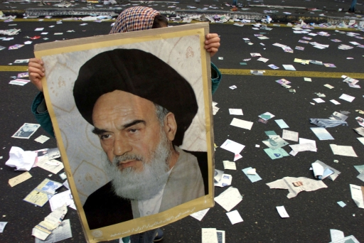 An Iranian girl carries a photo of the late leader of the Islamic revolution, Imam Khomeini, as she walks on a street covered with pre-election leaflets near Azadi Square in Tehran February 11, 2000.