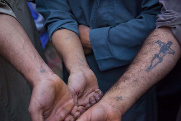 <p>Young Egyptian Coptic men display their Christian tattoos in October 2011. These tattoos are a rite of passage within the community and the pain felt while receiving them is seen as a small taste of the pain they believe Christ endured during the crucifixion.</p>
