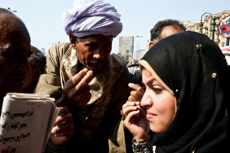 <p>A woman argues with a group of men in Tahrir Square in October 2011.</p>