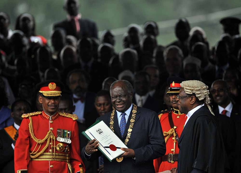 <p>Kenya's President Mwai Kibaki [C] smiles after being handed the signed constitution document by Attorney General, Amos Wako [R] on August 27, 2010 as Chief of General Staff, CGS, General, Jeremiah Kianga [L] looks on during the promulgation ceremony for Kenya's new constitution in the capital, Nairobi.</p>