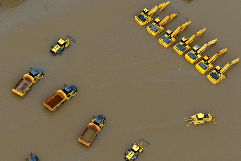 <p>Giant mining trucks and excavators are submerged as flood waters devastate much of Brisbane, the capital of Queensland state, on Jan. 13, 2011. Australia's third-largest city awoke to a