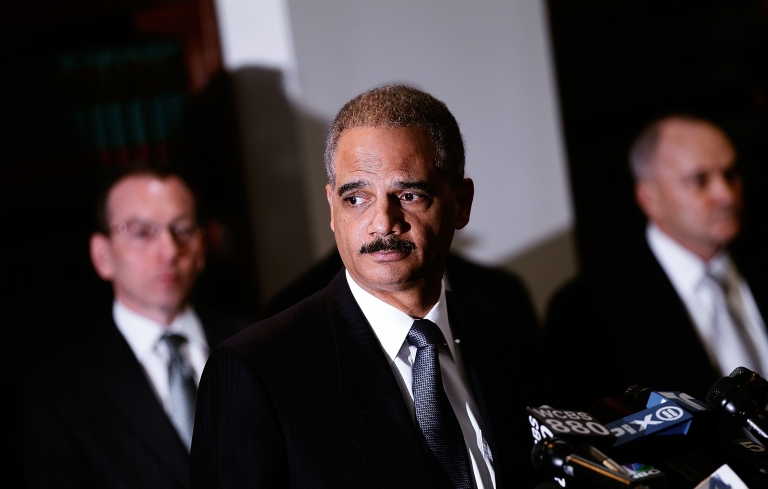 <p>United States Attorney General Eric Holder (center) stands with other officials during a press conference to announce a large-scale takedown of organized crime January 20, 2011 in New York City.</p>