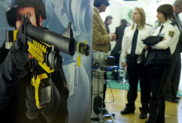 <p>A poster advertising the Taser X-12 shot gun which can deliver the Taser XREP electronic control device by arms manufacturer Mossberg is seen at the Taser stand at the European Police Congress in Berlin February 15, 2011.</p>