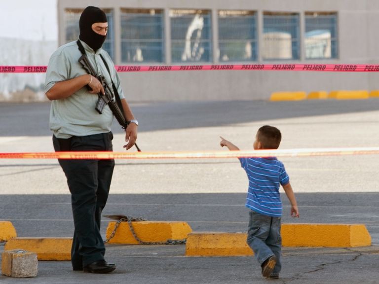 <p>A child look to the Ministerial Police stand next to truck with two bodies killed in Ciudad Juarez, Mexico, on April 08, 2011. An estimated 35,000 people have been killed since 2006 when President Felipe Calderon ordered a military crackdown on drug cartels.</p>
