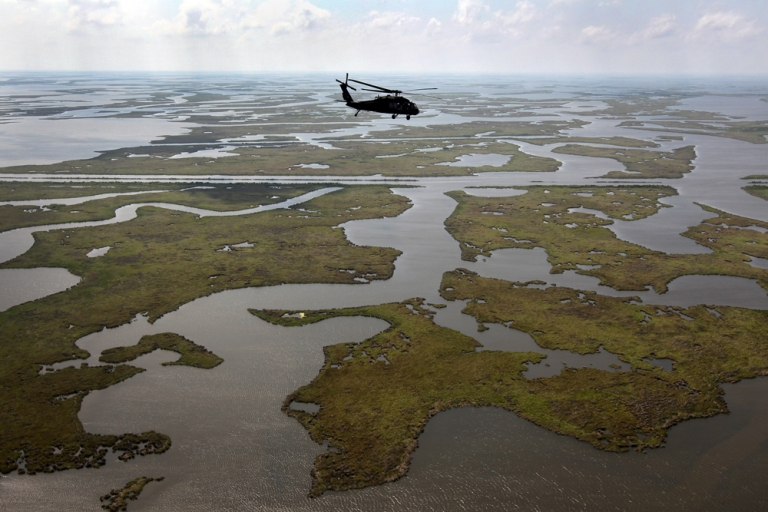 <p>A Louisiana National Guard blackhawk flies over marshland on April 19, 2011 in route to Middle Ground in southern Louisiana. The 2010 BP oil spill coated Gulf coast marshes and beaches.</p>