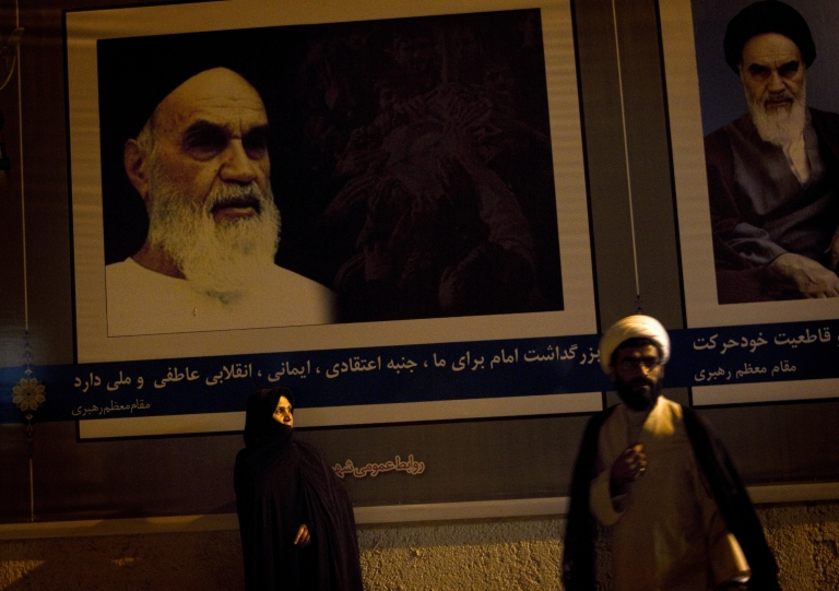 <p>An Iranian clergyman walks past a veiled woman standing under the portraits of Iran's late founder of Islamic Republic, Ayatollah Ruhollah Khomeini on June 3, 2011.</p>