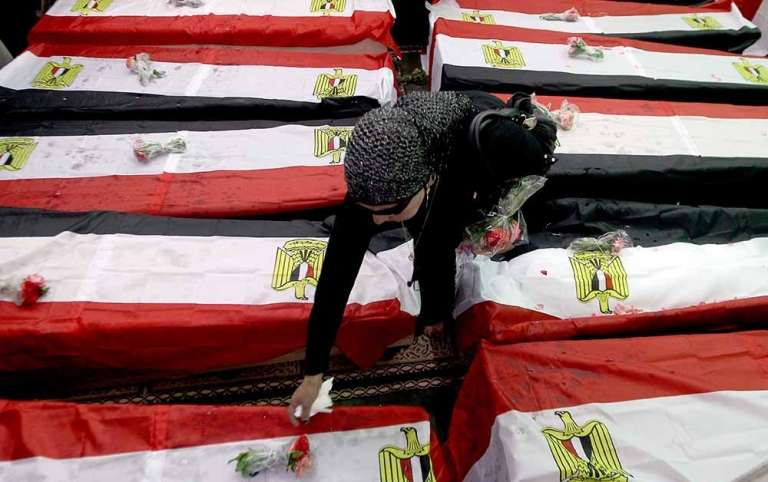 <p>An Egyptian woman lays flowers on the flag-draped coffins of 19 unidentified victims of Tahrir Square.</p>