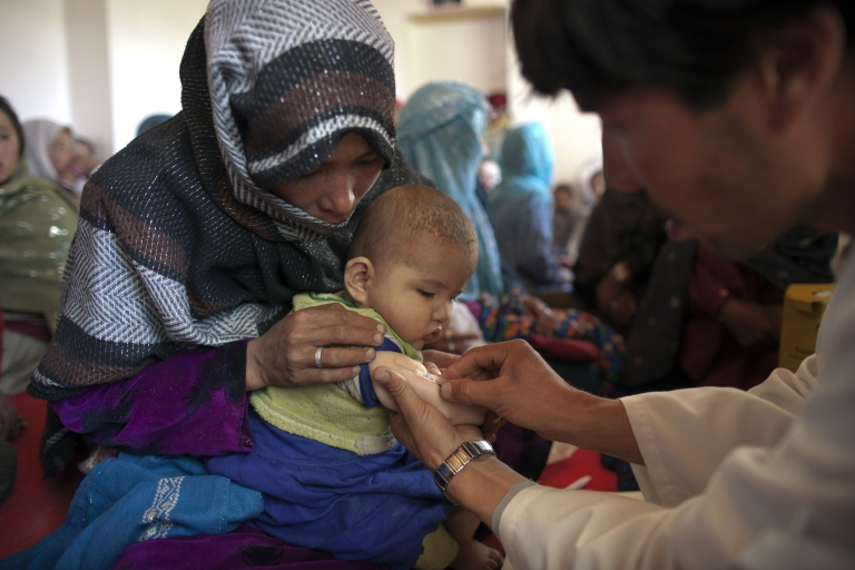 <p>Vaccinator gives a measles shot to a baby at a mobile health clinic in the mountain village of Raquol, in Panjab district, Afghanistan.</p>
