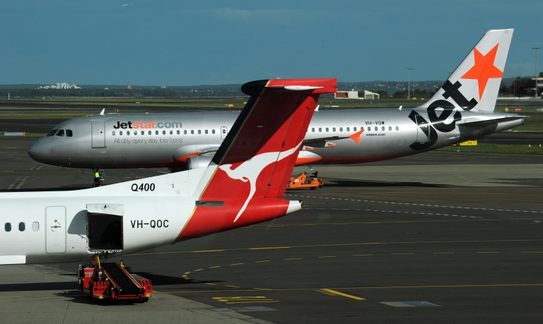 <p>A Jetstar plane (top) is seen taxiing past a Qantas plane (below) on the tarmac at the domestic airport in Sydney on June 21, 2011.</p>
