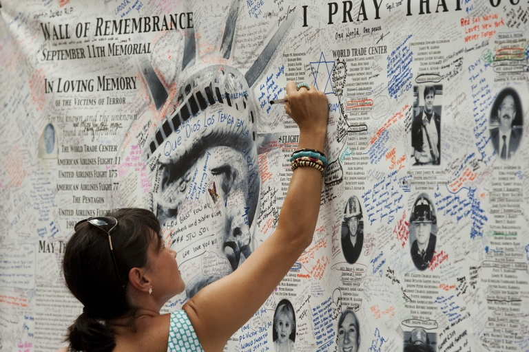 <p>A woman writes a message on the wall of remembrance memorial near the World Trade Center on Sept. 10, 2011 in New York. U.S. President Barack Obama on Saturday called for a