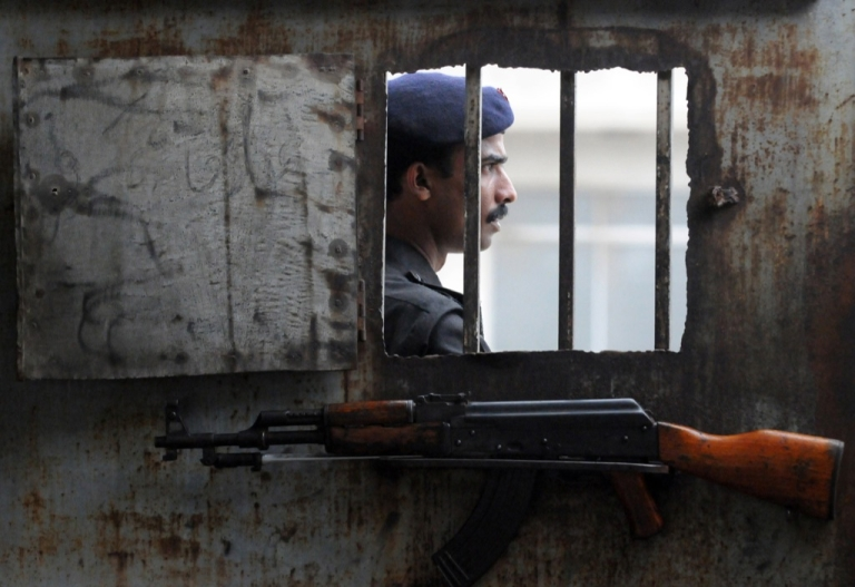 <p>A Pakistani policeman stands at the gate of an anti-terrorism court in Karachi on August 12, 2011.</p>