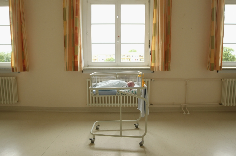 <p>A newborn baby sits in a bed Aug. 12, 2011 in a city in the east German state of Brandenburg, Germany.</p>