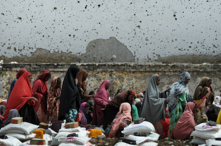 <p>Somali women walk past sacks of rice, flour and sugar donated to them and other Internally Displaced Persons (IDP) by a Kuwaiti based Islamic charity in Somalia's capital Mogadishu on August 14, 2011.</p>