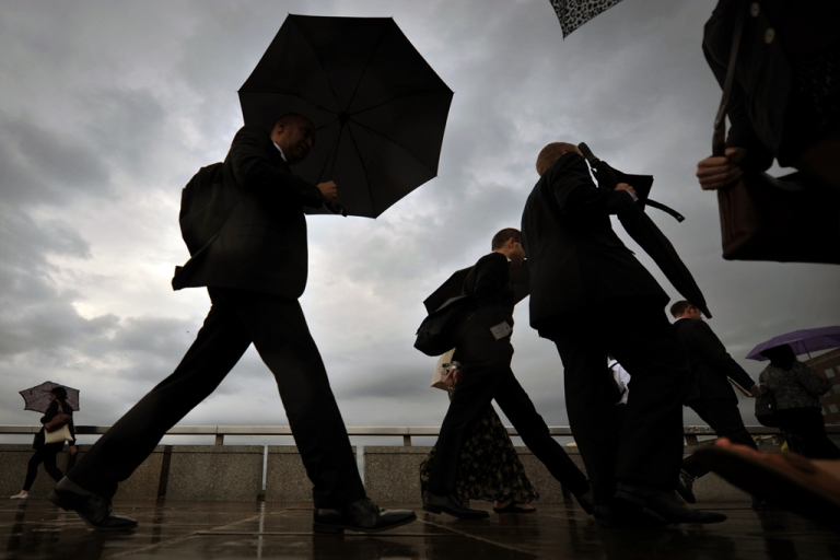 <p>City workers walk over London Bridge in central London, on August 18, 2011.</p>
