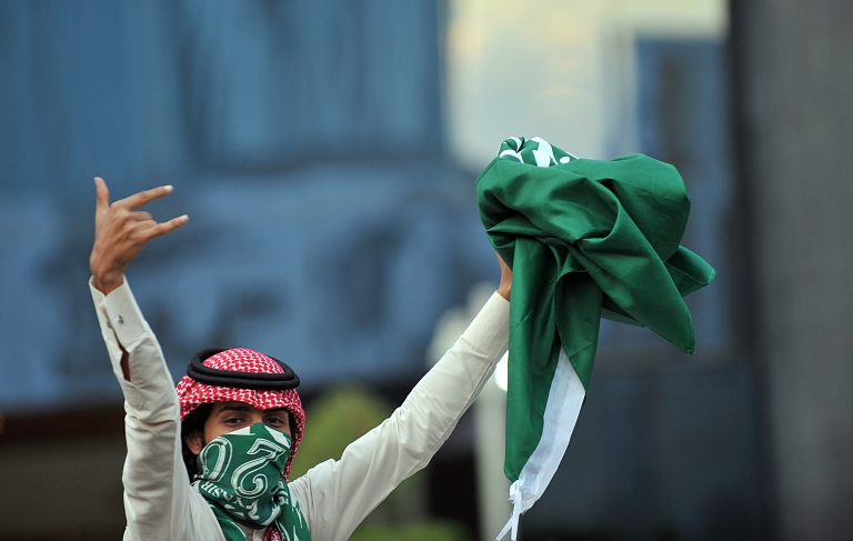 <p>A Saudi youth holds up a folded national flag during celebrations of the 81st Saudi Arabian National Day in the desert kingdom's capital Riyadh on September 23, 2011.</p>