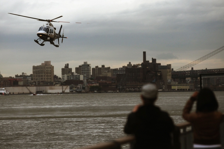 <p>A New York Police Department helicopter hovers over the East River before landing after a helicopter crash on October 4, 2011 in New York City during a birthday joyride.</p>