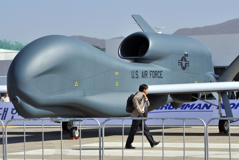 <p>A man walks past a US Air Force Global Hawk unmanned aerial vehicle hanger during a preview day of the Seoul International Aerospace and Defense Exhibition at a military air base in Seongnam, south of Seoul, on October 17, 2011.</p>