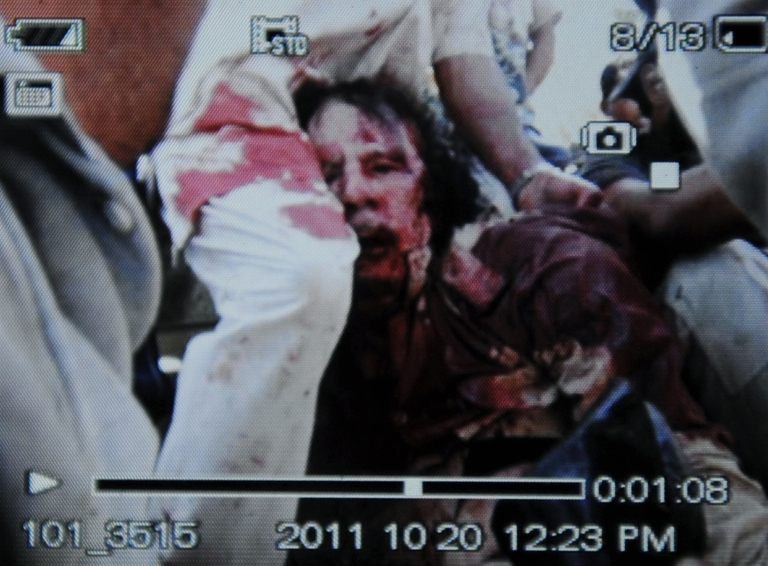 <p>An image captured off a cellular phone camera shows the arrest of Libya's strongman Moamer Kadhafi in Sirte on October 20, 2011. A Libyan National Transitional Council (NTC) commander had told AFP that Kadhafi was captured as his hometown Sirte was falling, adding that the ousted strongman was badly wounded.</p>