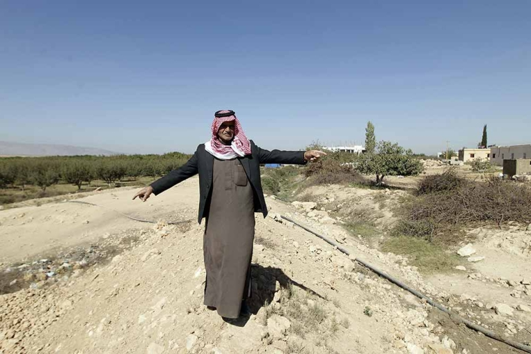 <p>A Lebanese man stands on a dirt barrier which separates Lebanon from Syria in the Bekaa Valley region of al-Qaa in eastern Lebanon on October 21, 2011. Syrian shells fell in the border region as violence continues to erupt in and around the restive city of Homs.</p>
