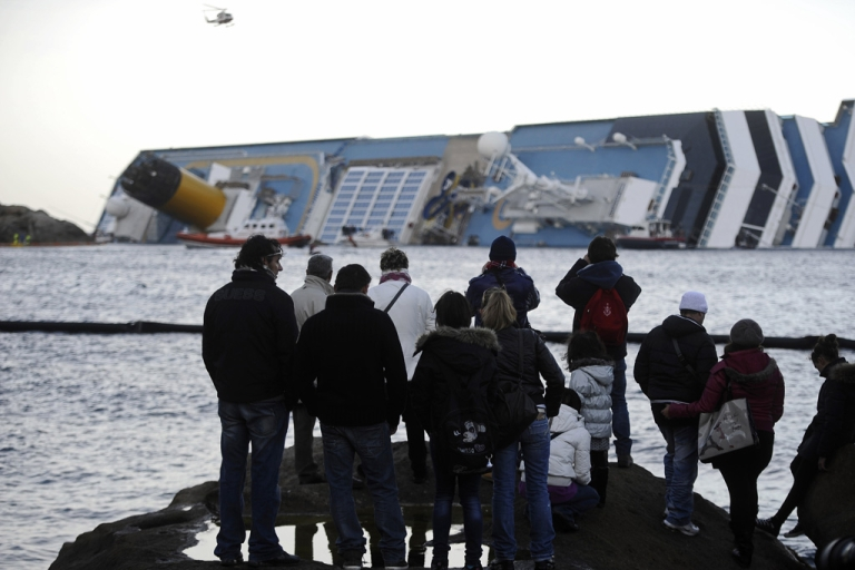 <p>People watch salvage and recovery efforts today aboard the Costa Concordia, which ran around off the Isola del Giglio a week ago. Divers searching the cruise ship wreck found a 12th body.</p>