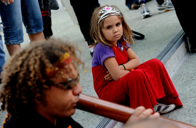 <p>A young girl (R) watches as a protester plays a didgeridoo as the Commonwealth Heads of Government Meeting (CHOGM) starts in Perth on 28 October 2011.</p>