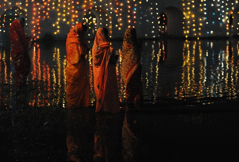 <p>Nepalese Hindu devotees worship the rising sun as they stands in the Rani Pokhari during the Chhath festival, which honours the Sun God, in Kathmandu on November 2, 2011.</p>