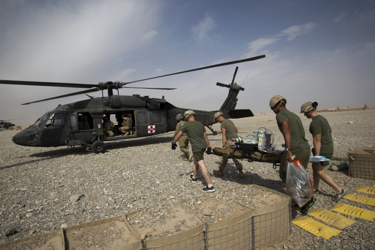 <p>US Navy medical officers carry a wounded US Marine who was hit by an Improvised Explosive Device (IED) after amputating his leg to a medevac helicopter of US Army's Task Force Lift 'Dust Off', Charlie Company 1-171 Aviation Regiment in Helmand province on November 2, 2011.</p>