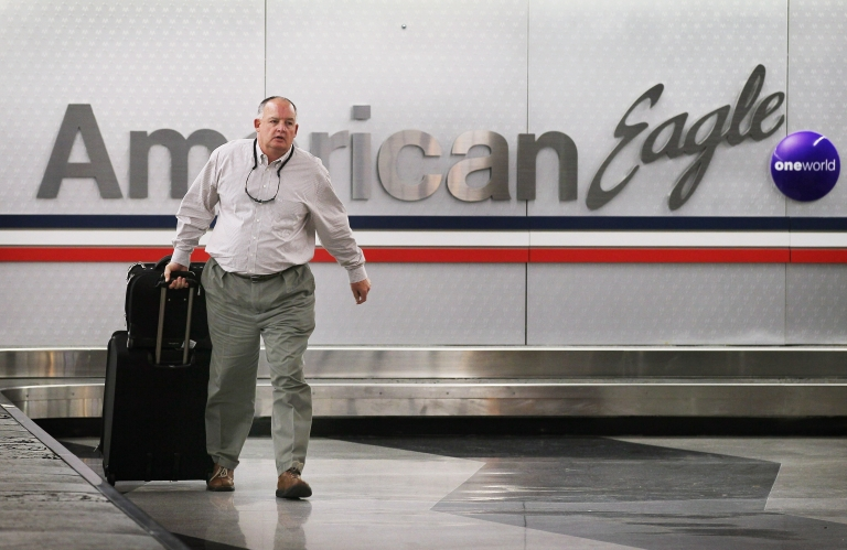 <p>A passenger retrieves his luggage from a baggage conveyor that services American Eagle Airlines at O'Hare Airport on November 14, 2011 in Chicago, Illinois.</p>