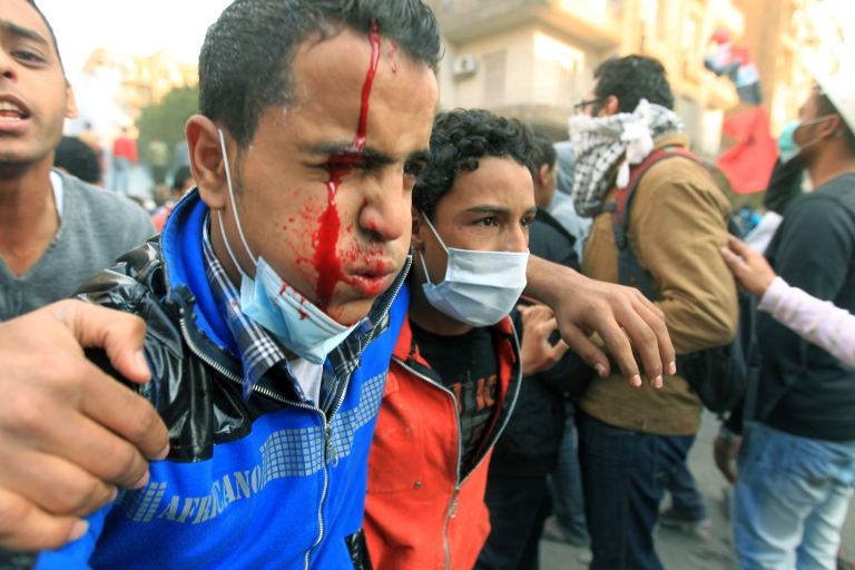 <p>An injured Egyptian protester is helped away on the third day of clashes at Tahrir Square in Cairo on November 21, 2011. Fresh violence erupted between police and protesters demanding the end of army rule, as the ruling military council faced its worst crisis since Hosni Mubarak was toppled.</p>