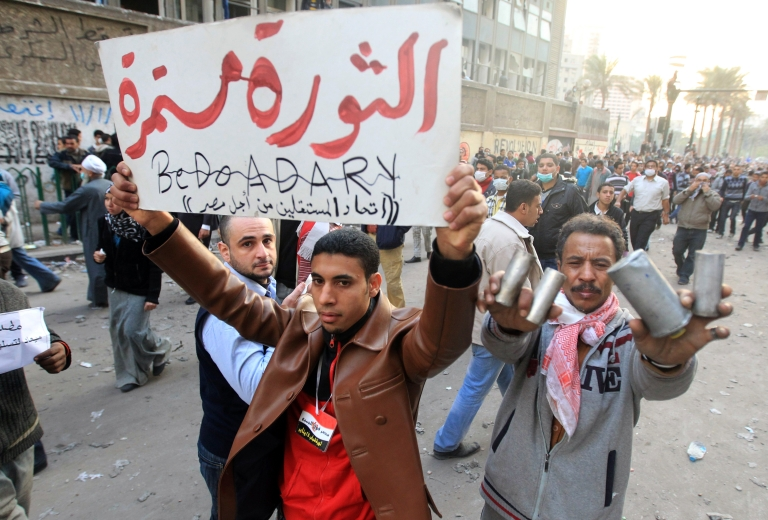 <p>An Egyptian man holds up a banners that reads in Arabic,