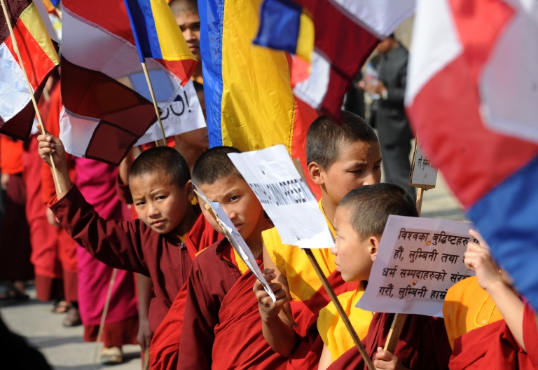 <p>Nepalese Buddhist monks hold Buddhist flags and placards during a peace rally in Kathmandu on December 7, 2011.The organizers claimed that the Nepalese Buddhists have been unjustly bearing the discrepancies of Nepal's One China policy, which recognizes Tibet as its integral part.</p>