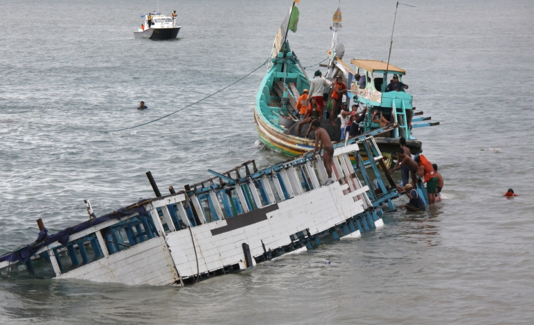 <p>Rescuers check the wreckage of a people smuggler's boat seen half submerged after being towed near the coast of Puger village in East Java province on Dec. 21, 2011. Indonesian police arrested eight people December 22 in connection with an overloaded boat carrying 250 asylum seekers that capsized en route to Australia, as the confirmed death toll reached 90.</p>