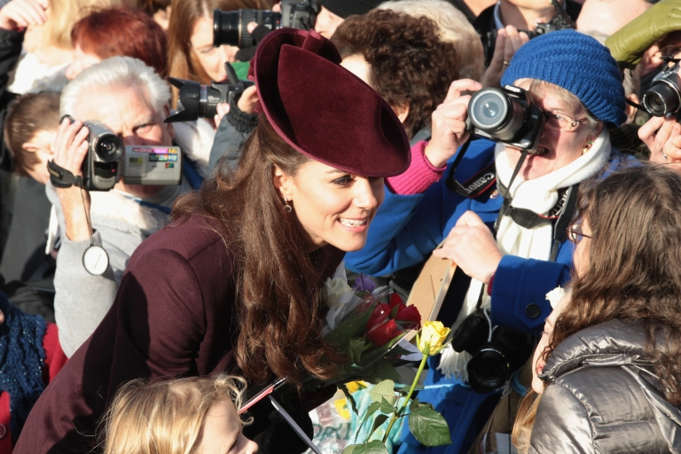 <p>Kate Middleton, Duchess of Cambridge, accepts flowers from members of the crowd as she leaves Sandringham Church after the traditional Christmas Day service on December 25, 2011, in King's Lynn, England.</p>