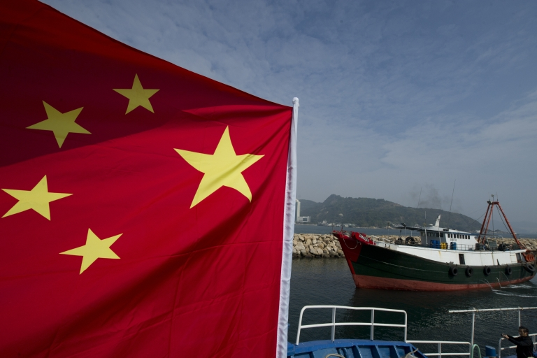 <p>A fishing boat (R) sails past another boat flying a Chinese flag and piloted by an activist organization that asserts Chinese sovereignty over a group of uninhabited islets, known as Senkaku in Japan and Diaoyu in China, before it sets sail for the islets in Hong Kong on January 3, 2012.</p>