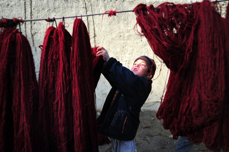 <p>An Afghan child hangs yarn to dry as he works at a home industry workshop in Mazar-i-Sharif on January 2, 2012. Some of the children work in the mornings and go to school in the afternoons. A single carpet may earn a family 12,000 to 13,000 Afghanis (242 to 262 USD) -- paid on completion -- but are usually sold for more in shops. UNICEF said in 2007 that a quarter of Afghan children aged between seven and 14 worked, despite legal and constitutional protection and Afghanistan being a signatory to the UN Convention on the Rights of the Child.</p>