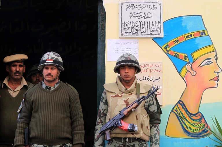 <p>Egyptian soldiers stand guard near a mural of Queen Nefertiti outside a polling station in Minya, some 350 kms south of Cairo, during the third and final round of landmark parliamentary elections on January 3, 2012.</p>